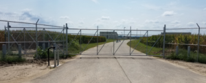 Airport secured by a chain link cantilever gate with key pad entry and barb wire