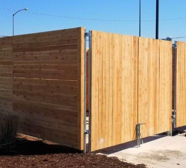 Custom wood dumpster enclosure with metal framework and solid wood pickets
