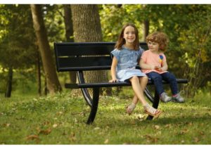 A park bench with a brother and sister sitting side by side