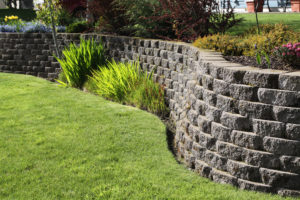 Well landscaped wall of cement cobblestone bricks with grass and ornamental plants