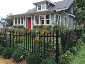 Alternating picket ornamental fence installed in front of a garden in the front yard of a house
